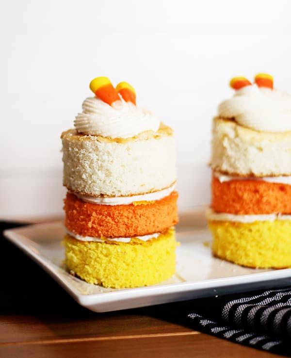 mini round cakes with yellow, orange, and white layers